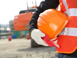 Man holding hard hat on construction site