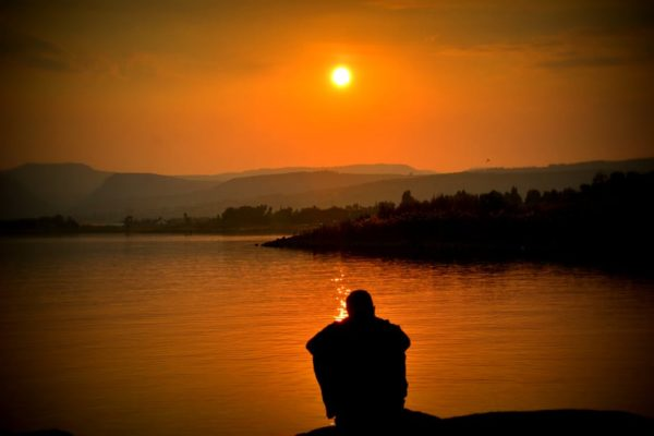 Man sitting near water during sunset