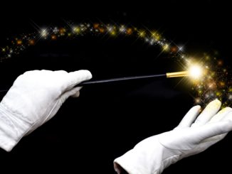 White gloved hands holding a magic wand