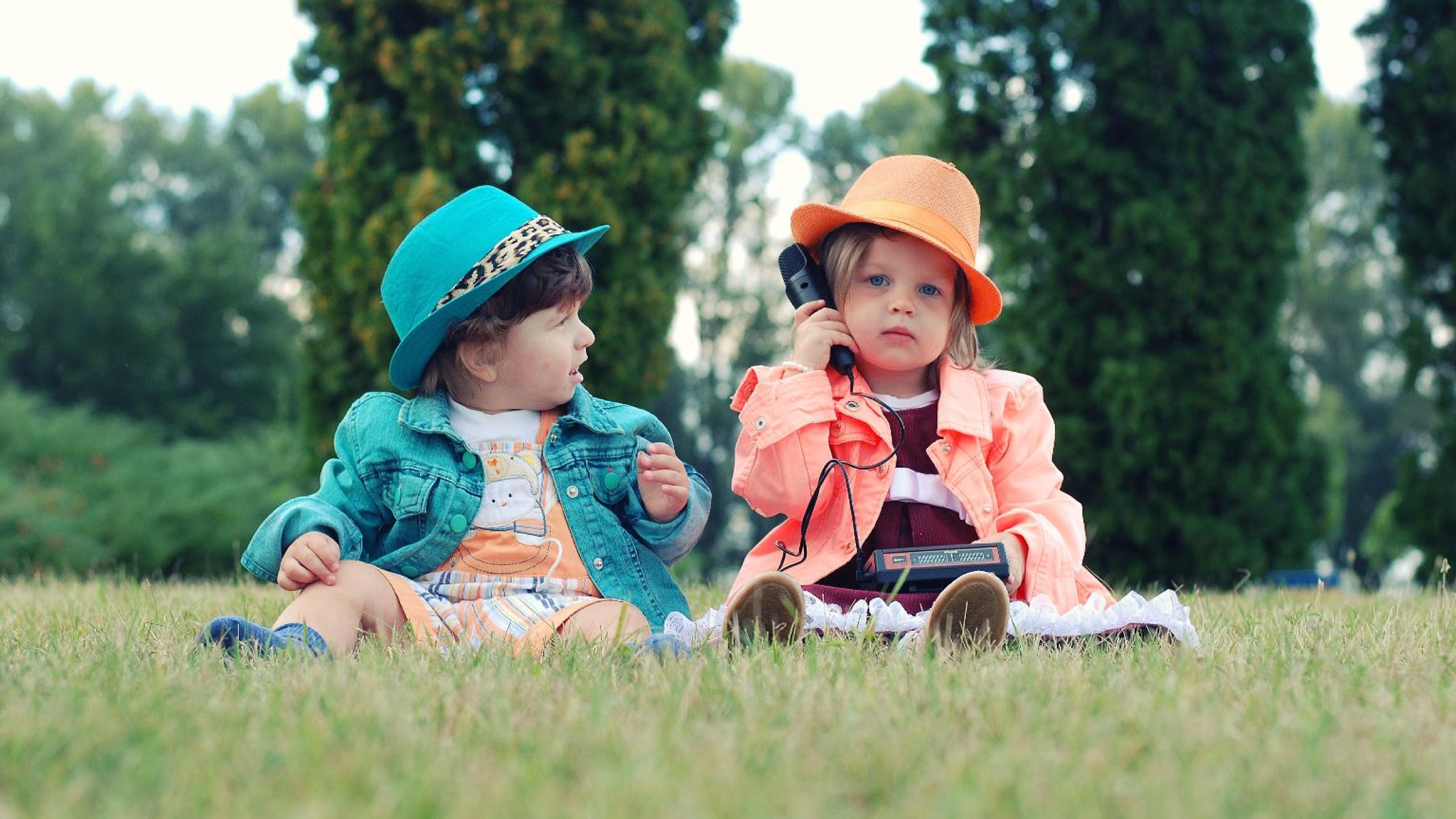 Two small children in colorful, adult-looking hats and jackets