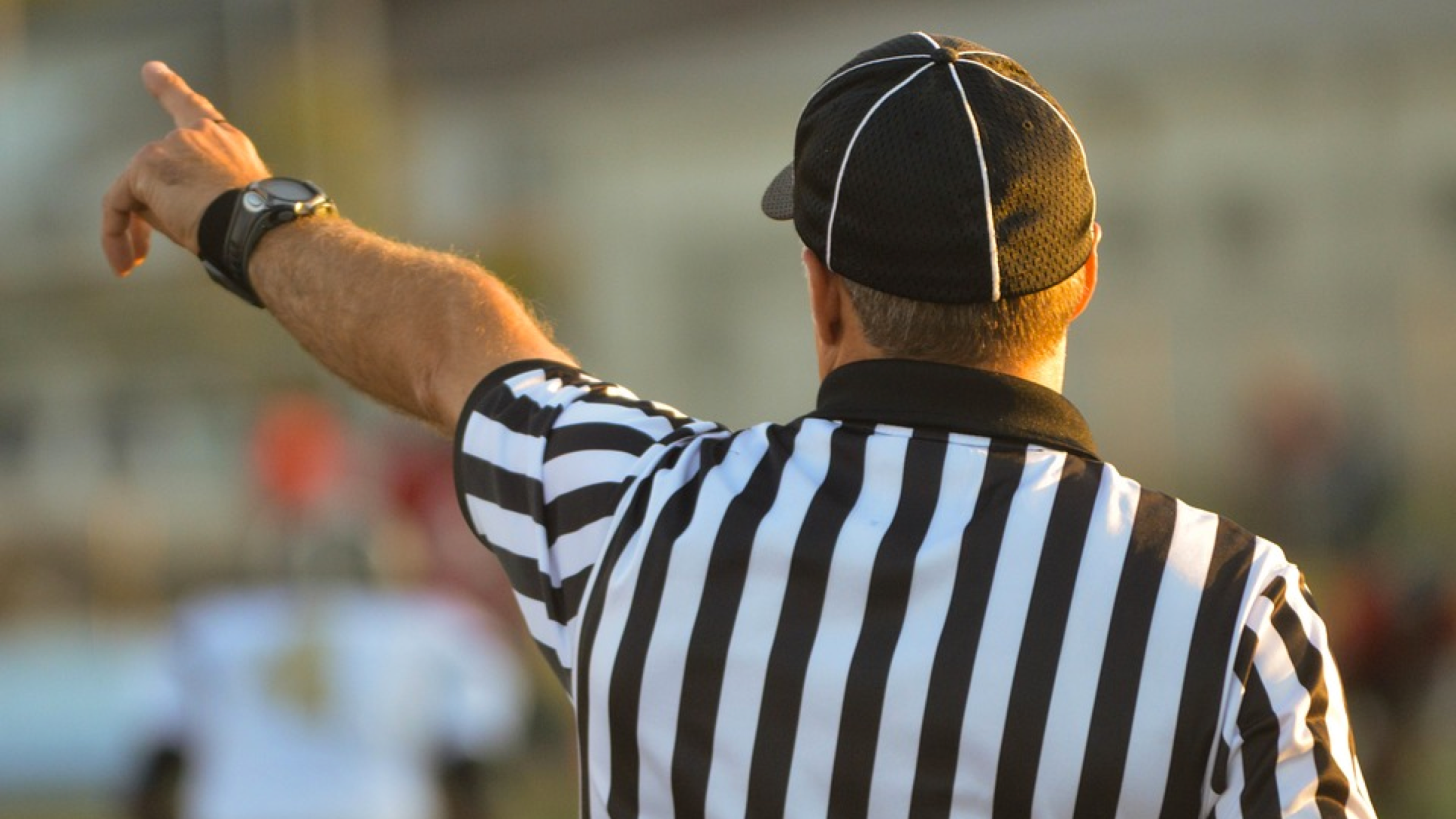 Sports referee in striped black and white shirt pointing